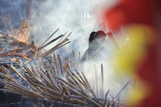 source: Tao Zhang/NurPhoto via Getty Images | Chinese worshippers light incense as they pray at the Dacheng Temple on Jan 28, 2017 in Qiqihar, China.