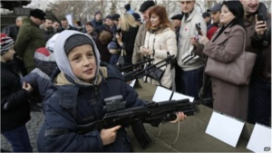 A child in Sevastopol plays with a weapon displayed as part of a promotional campaign by the Russian Army. Source: BBC News.